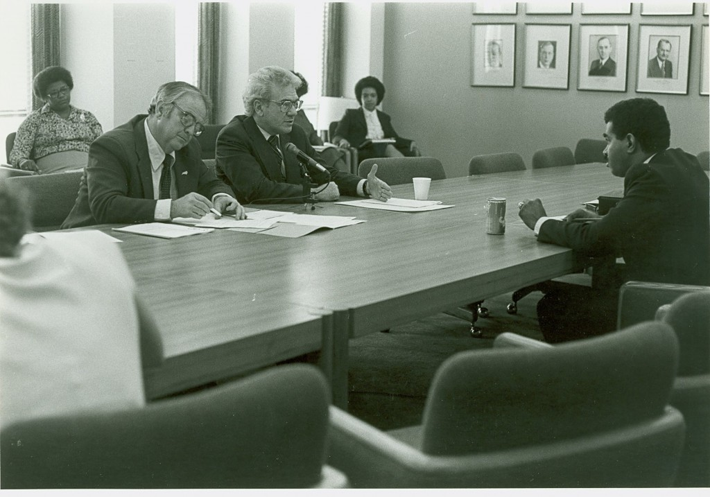Ernest L. Boyer and other unidentified people at a board meeting in the Office of Education. - BCA