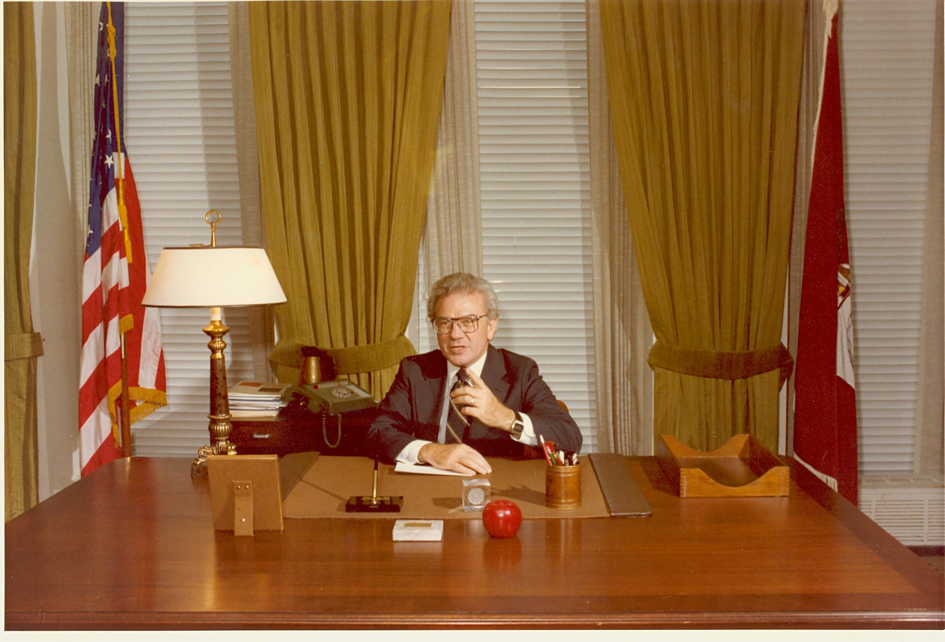 Ernest L. Boyer sitting at his desk at his welcoming party to Washington, DC as the new Commissioner of Education. - BCA